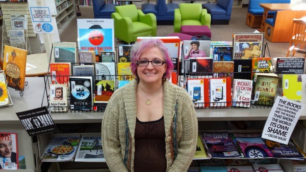 Jama Watts proudly poses in front of her banned books display.