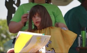 A girl, book in hand, cashes in on her free haircut at the Little Free Library festival.