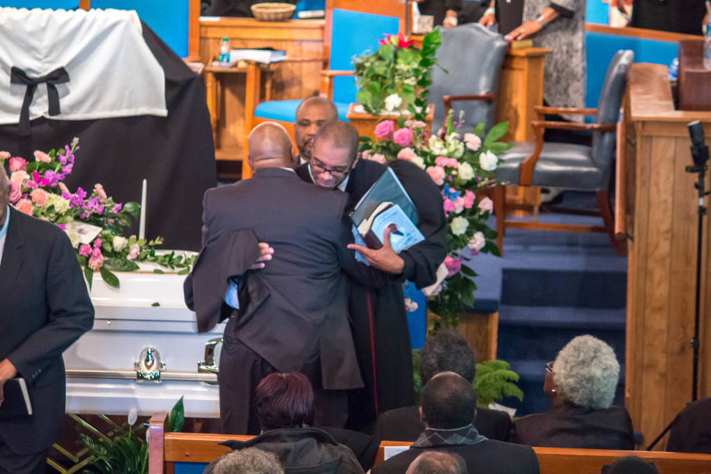 Reverend Stacey Evans embracing Deacon Blount at his mother-in-law's Mrs. Lonnie Mae Dreighton home-going service.