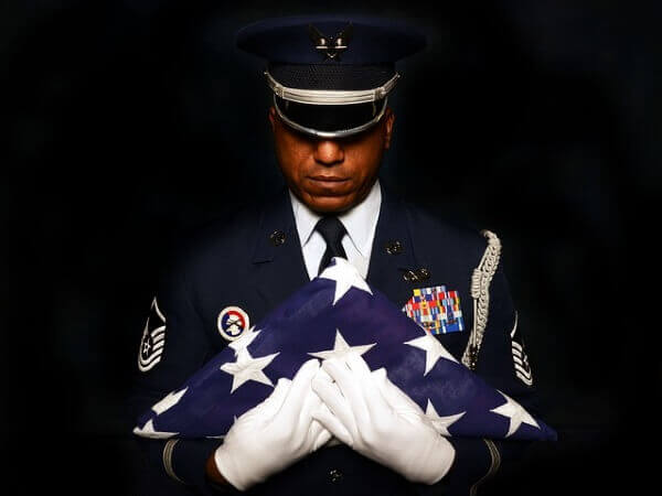 A grieving military veteran holding a burial flag