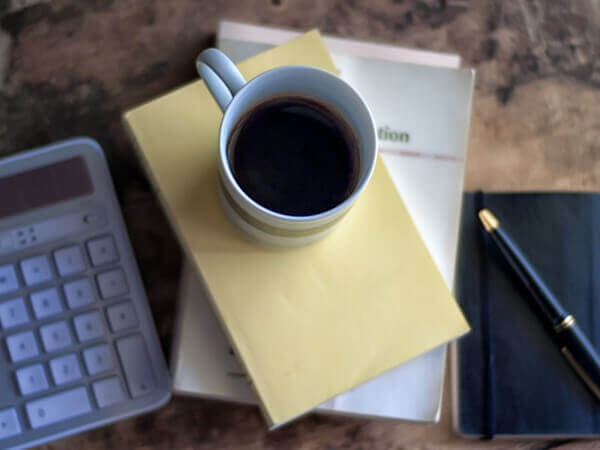 background image of a coffee cup sitting on a stack of papers with a calculator and pen in the background