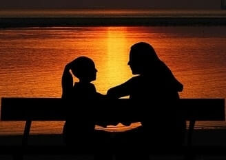adult talking to a child near ocean