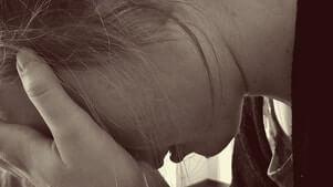 grieving woman head in hands