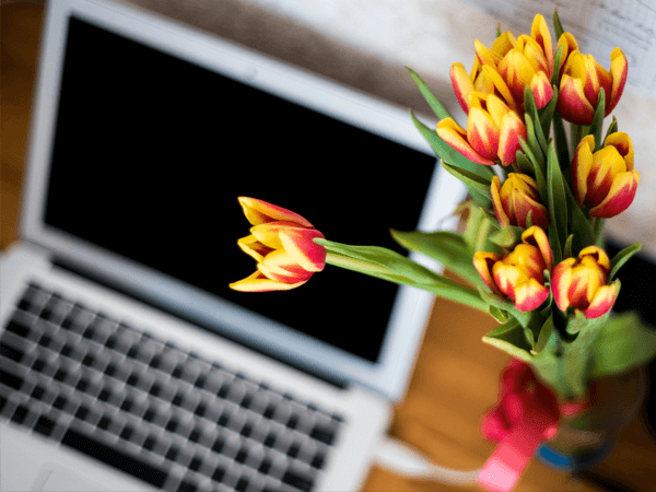 Image of flowers with computer in the background