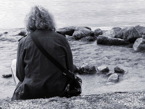 Sad Woman sitting on a large rock by the ocean