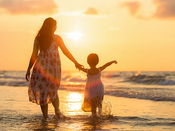 image of a woman and young child walking on the beach towards the sunset