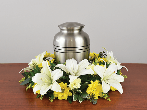 silver urn on a table with flowers around it