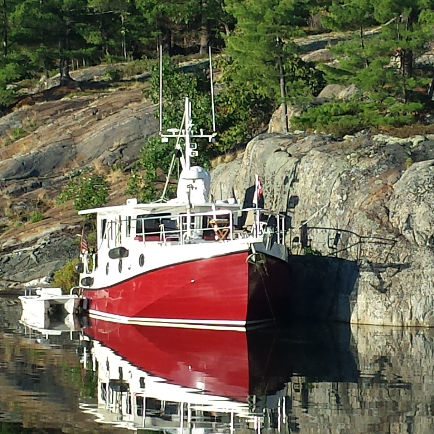 Red and White Boat Docked By Giant Rock Mountains