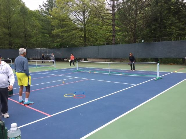 About 25 people attended the open house at Brookside. NJPA members showed them how to play. George set up Simon the ball machine for everyone to use and practice strokes
