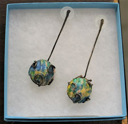 Using a torch, oil, pigments, and gold leaf to create colored metal jewelry.