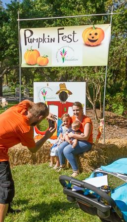 father takes a photo of mother and child in front of pumpkin fest face cut out