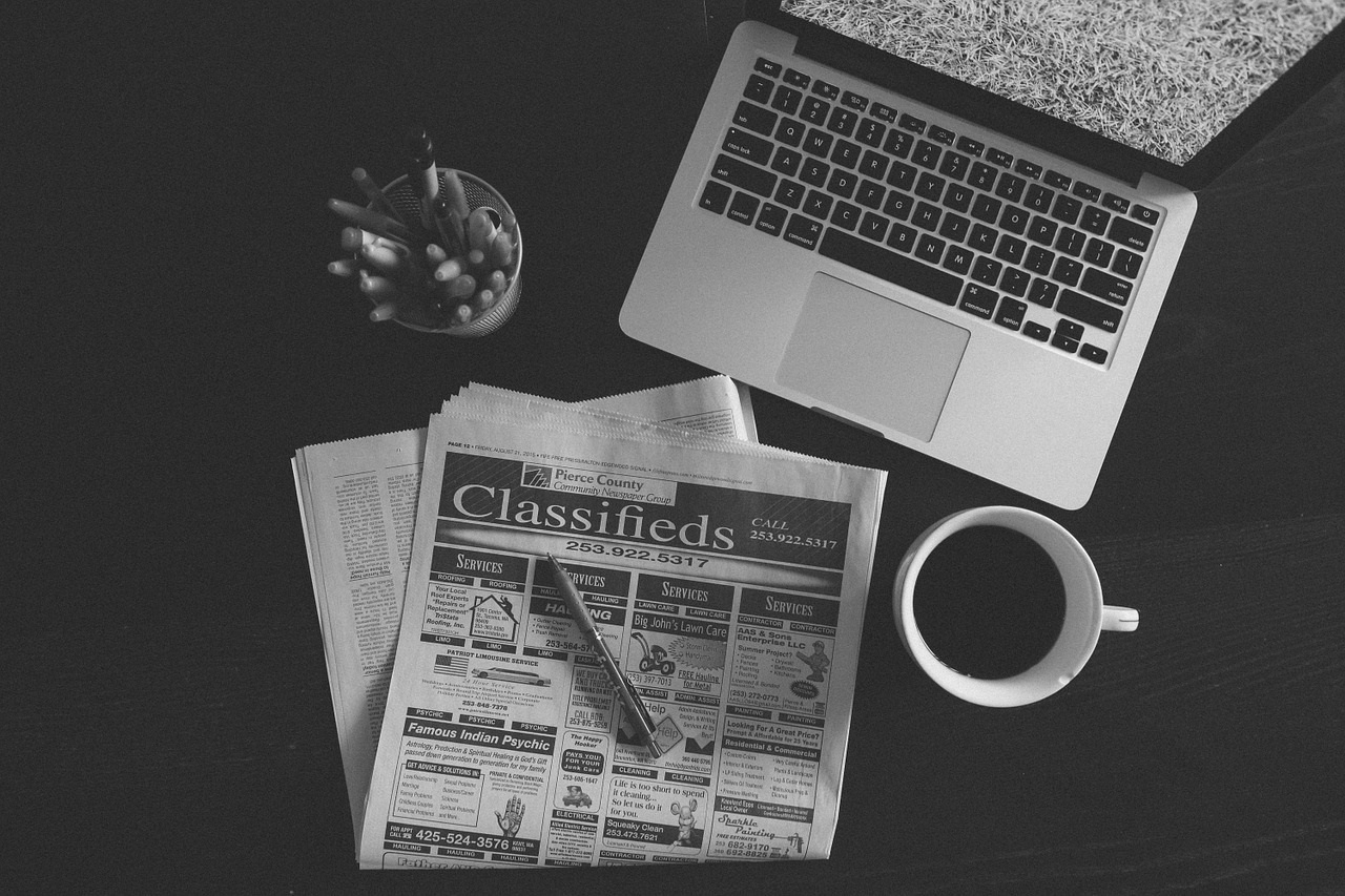 Newspaper Classifieds, Laptop and Coffee on a Desk