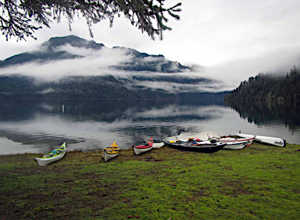 kayaks lined along the grassy shore at lake crescent