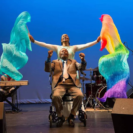 women with colored silks and man in wheelchair