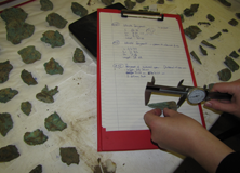 Archaeologist recording finds that included pottery, coins, tools, and other Romano-British objects.