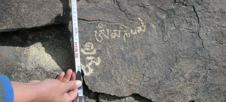 A team member uses a tool to indicate the scale of a petroglyph.