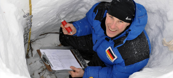A volunteer records the temperature of the snow at various depths.