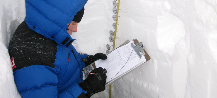 A volunteer takes the temperature of the snowpack.