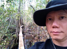 Dr. Chow in front of a footbridge between forest and marshes.