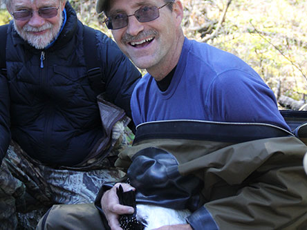 Dr. Jim Paruk holding a common loon, the subject of his research
