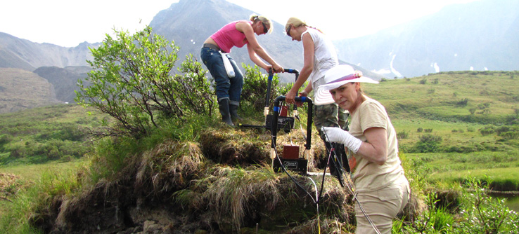 Research team collecting soil samples from Arctic tundra