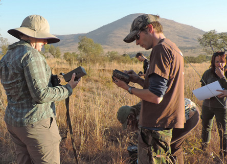 Expedition team members prepare a camera trap site at South Africa's Pilanesberg National Park. © Jill Gossett, Lincoln Park Zoo.