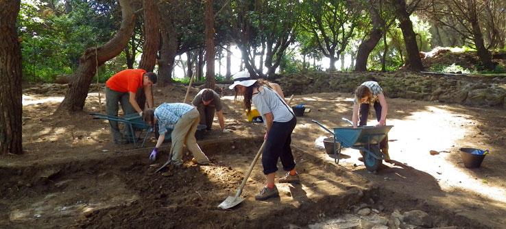 Volunteers carefully remove dirt from the villa's foundation.