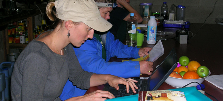 Earthwatch researchers recording fieldwork data on a laptop