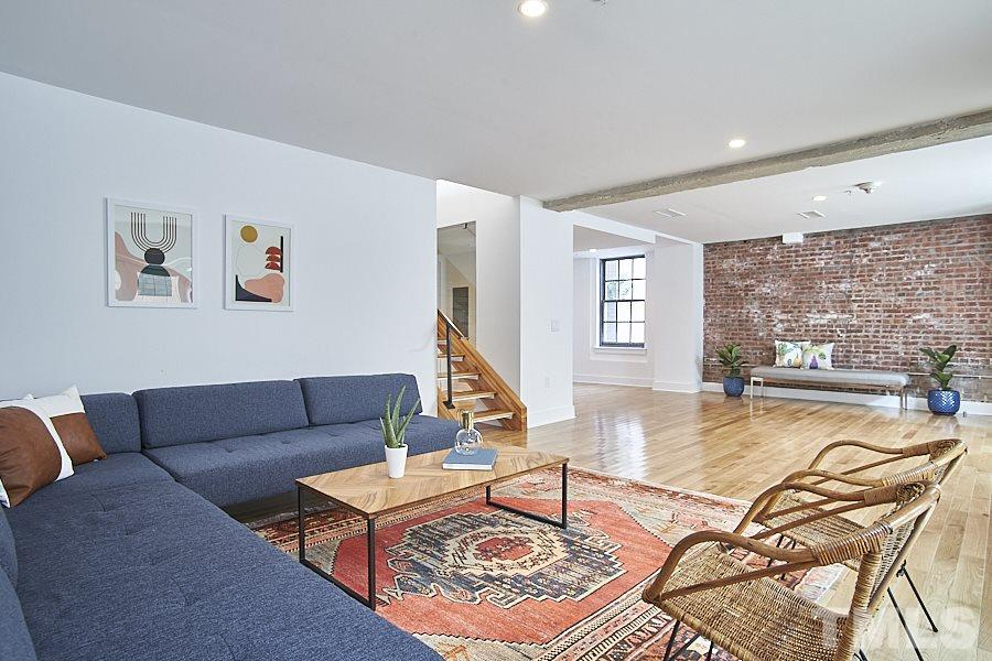 Exposed brick wall and original ceiling beam contribute to the many textures within the unit.
