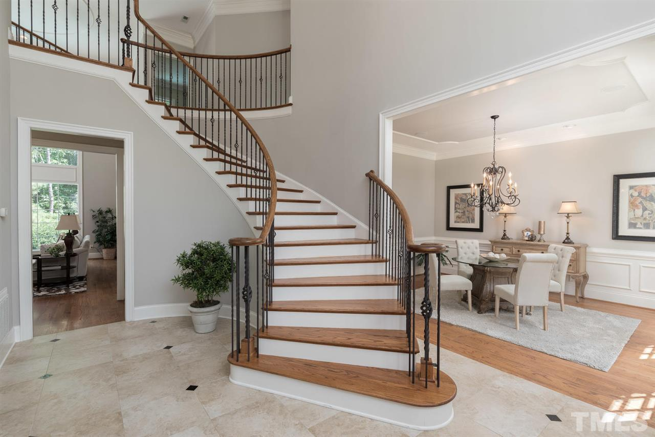with sweeping staircase and marble floors.