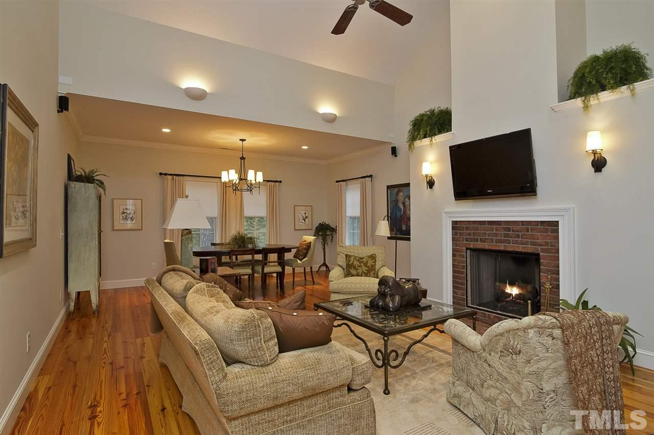 Soaring ceilings, brick fireplace and rich wood floors provide ambient living space.