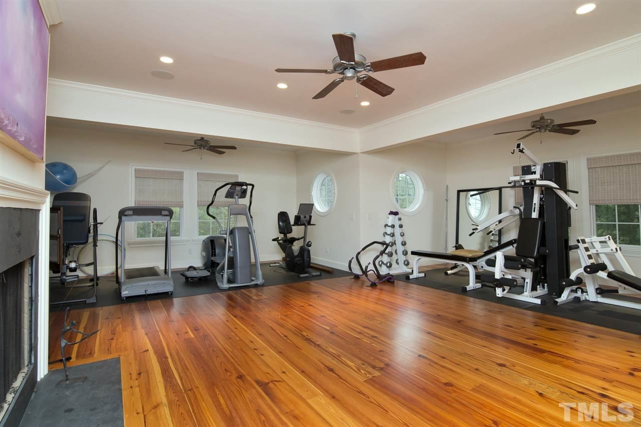 Spacious fitness room can also serve as a second grand living room with large windows and even a fireplace.