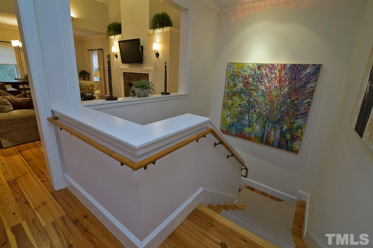 Wide stairway with beautiful track lighting for art display.