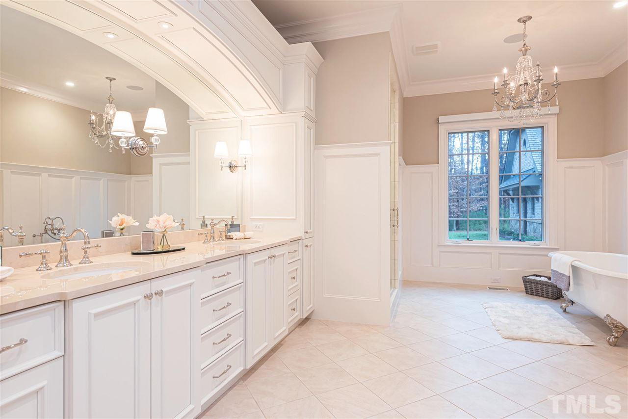 Oversized master bath retreat, custom cabinetry w/ abundance of storage, crystal chandelier, lady's vanity area, double sinks, top of line fixtures, freestanding claw foot bathtub w/ wall mounted tv, steam shower-temp, light & music controlled w/Thermasol