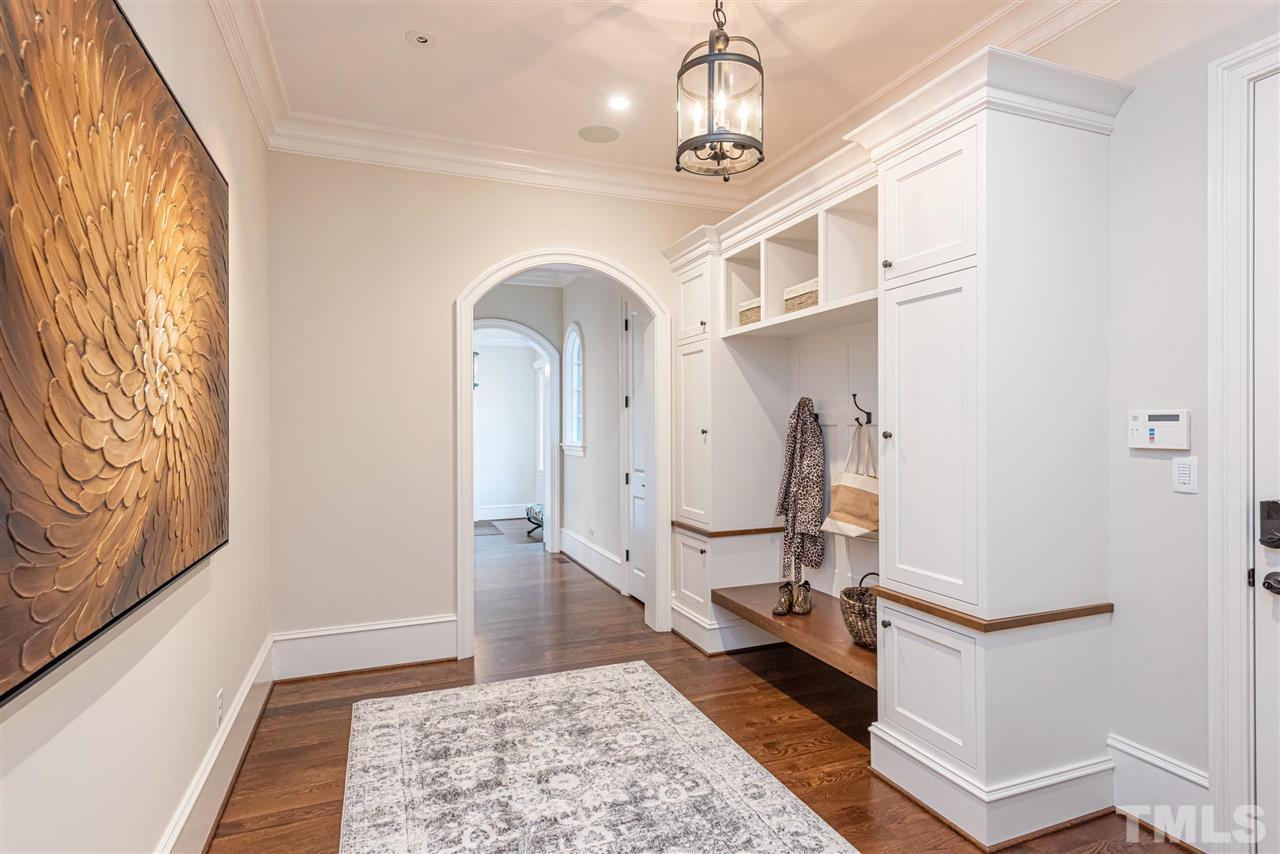 Side entry off porte cochere & garage. Built in cabinetry w/ hooks & storage & powder room. Accessible to the audio/video hub & add storage area-epoxy floors, & double wood doors lead to outside-perfect area for storing motorcycle, yard equip, toys