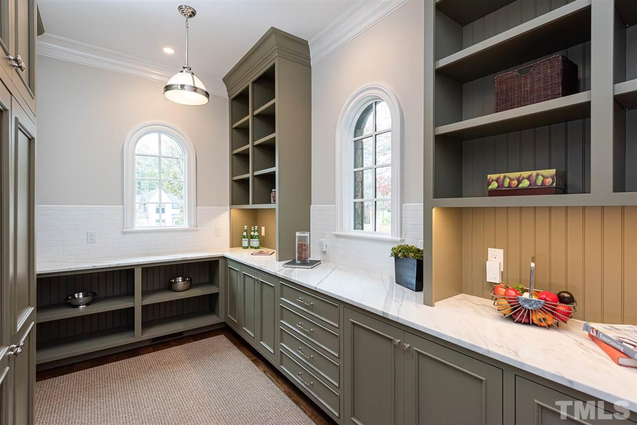 Sage green custom inset cabinets, dedicated prep space & storage area next to kitchen. Ample counter space, calcutta