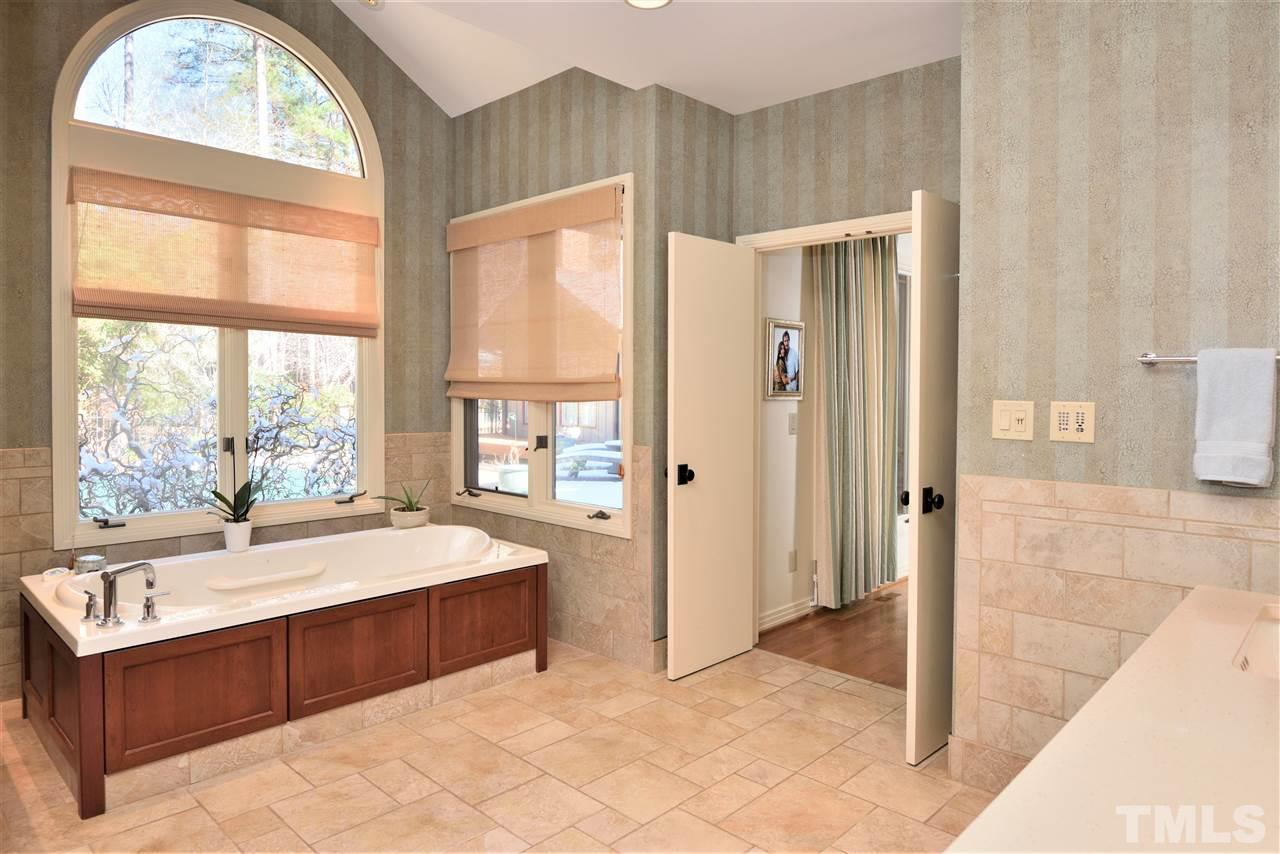 Master bath features a generous air-jet whirlpool and massive open shower with seat and rain forest shower head