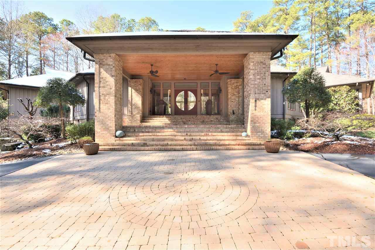 Circular asphalt drive accented with pavers leads to the grand covered entrance overlooking serene water feature