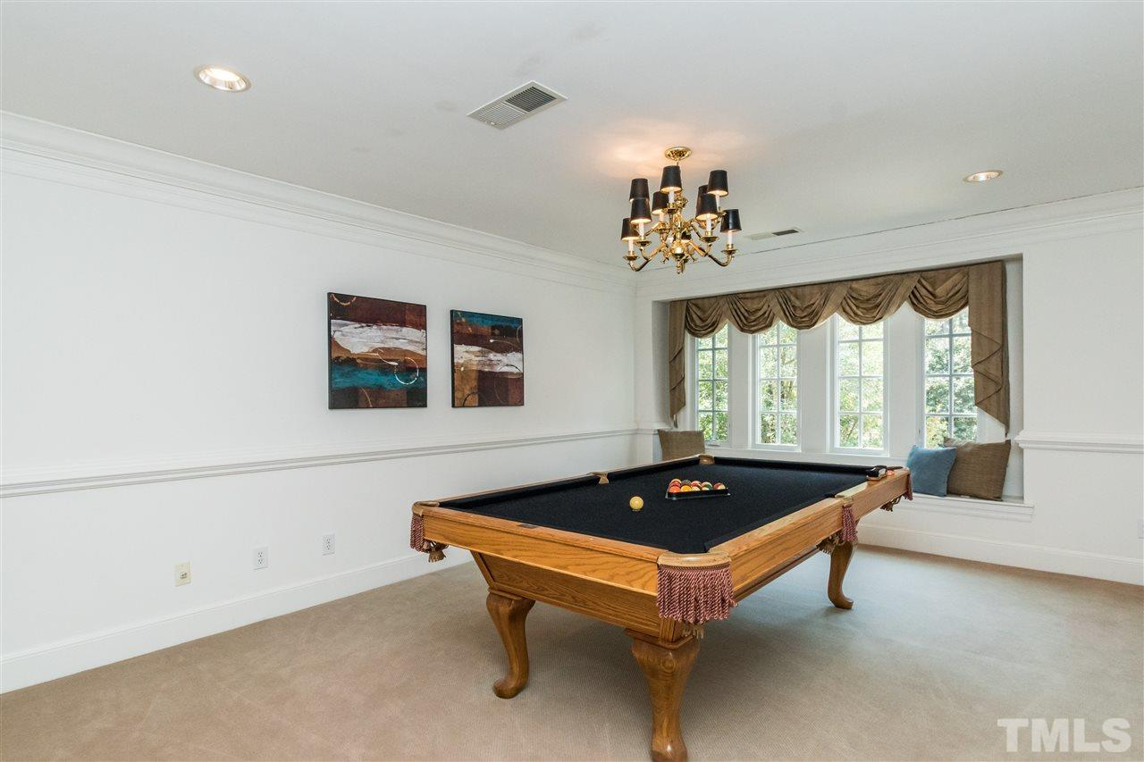 Upstairs billiard or game room with window seat. Could also be a bedroom by tying into the adjacent bed/bath suite.