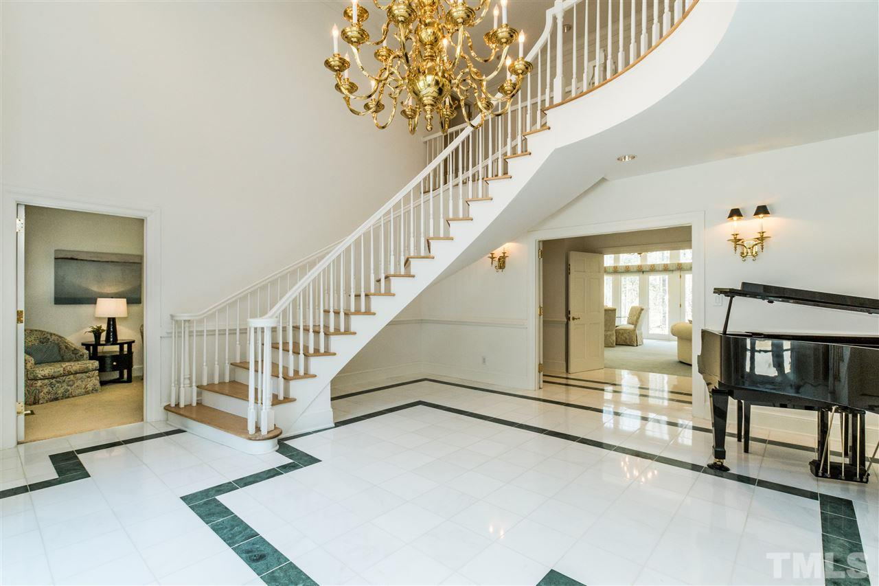 A grand 2 story foyer with floating hardwood staircase welcomes you upon entry into the home.