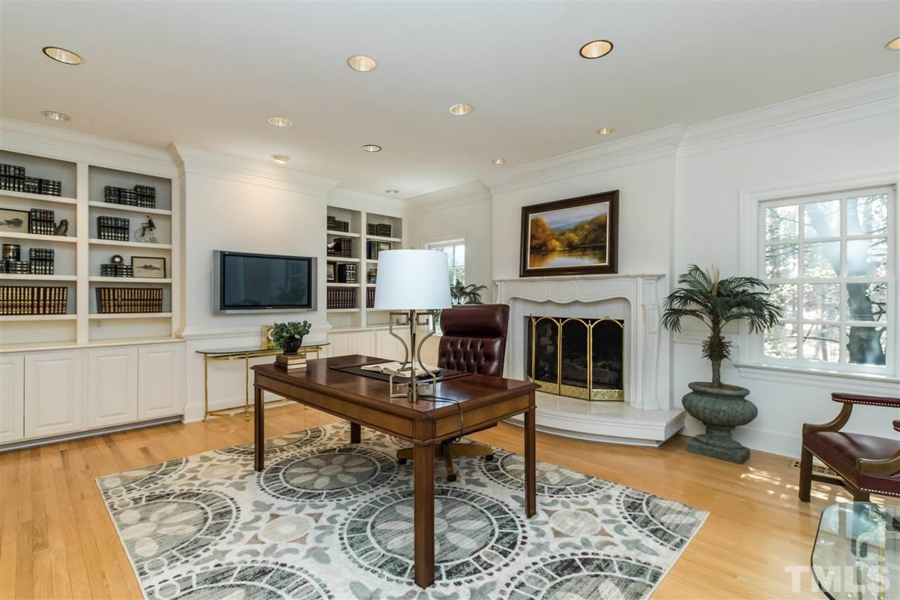 An executive office/study/library with gas marble surround fireplace, and hardwood floors.