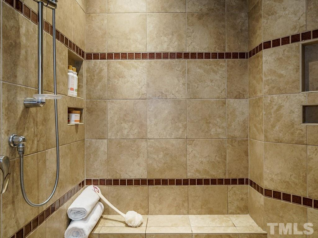 Double shower heads and lots of ceramic tile and pebble-stone floor.