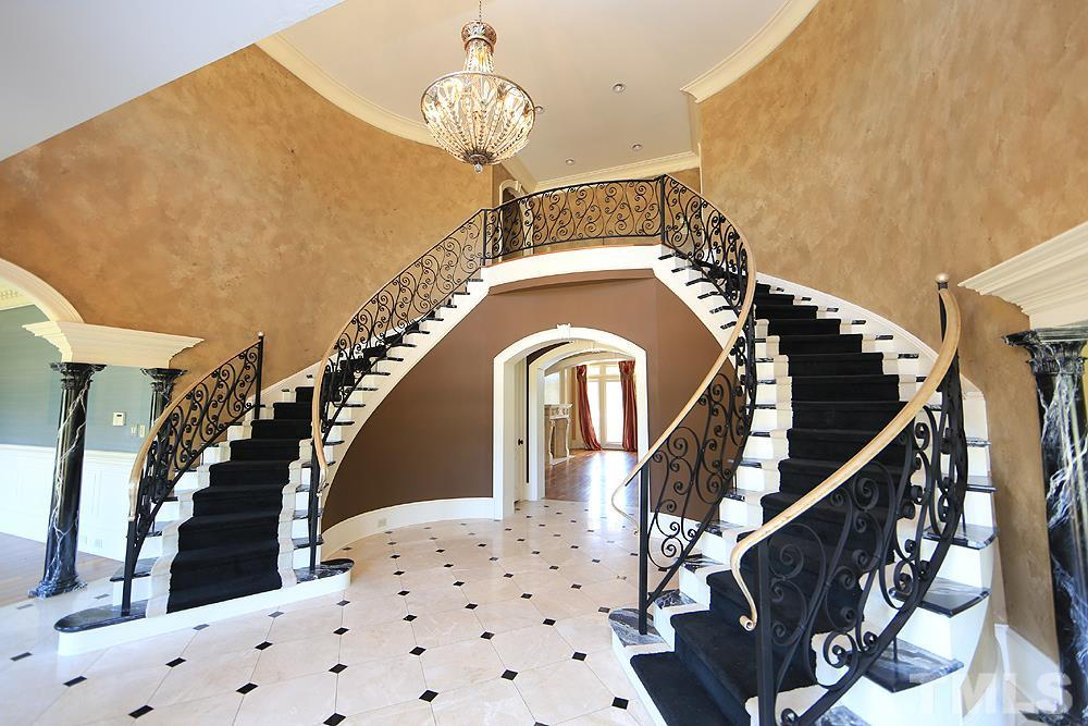 Dual winding staircases outline the foyer, 2 story ceiling,catwalk & balcony offers sweeping views. Pillars separate both formal dining and living rooms. Views to the front entry & circular drive!