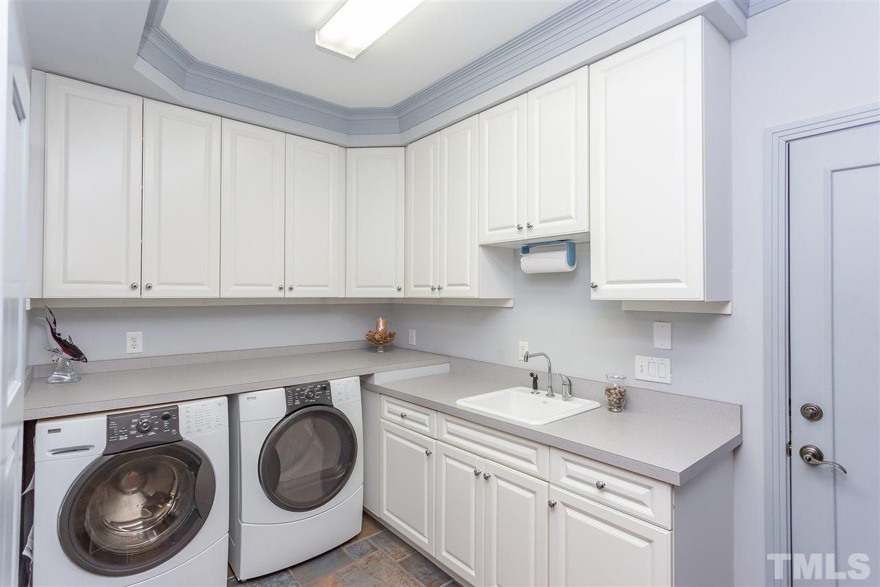 The first floor laundry is located between the garage and the hall to the butler's pantry leading to the kitchen area.  It has storage and also serves as the mudroom with its location.