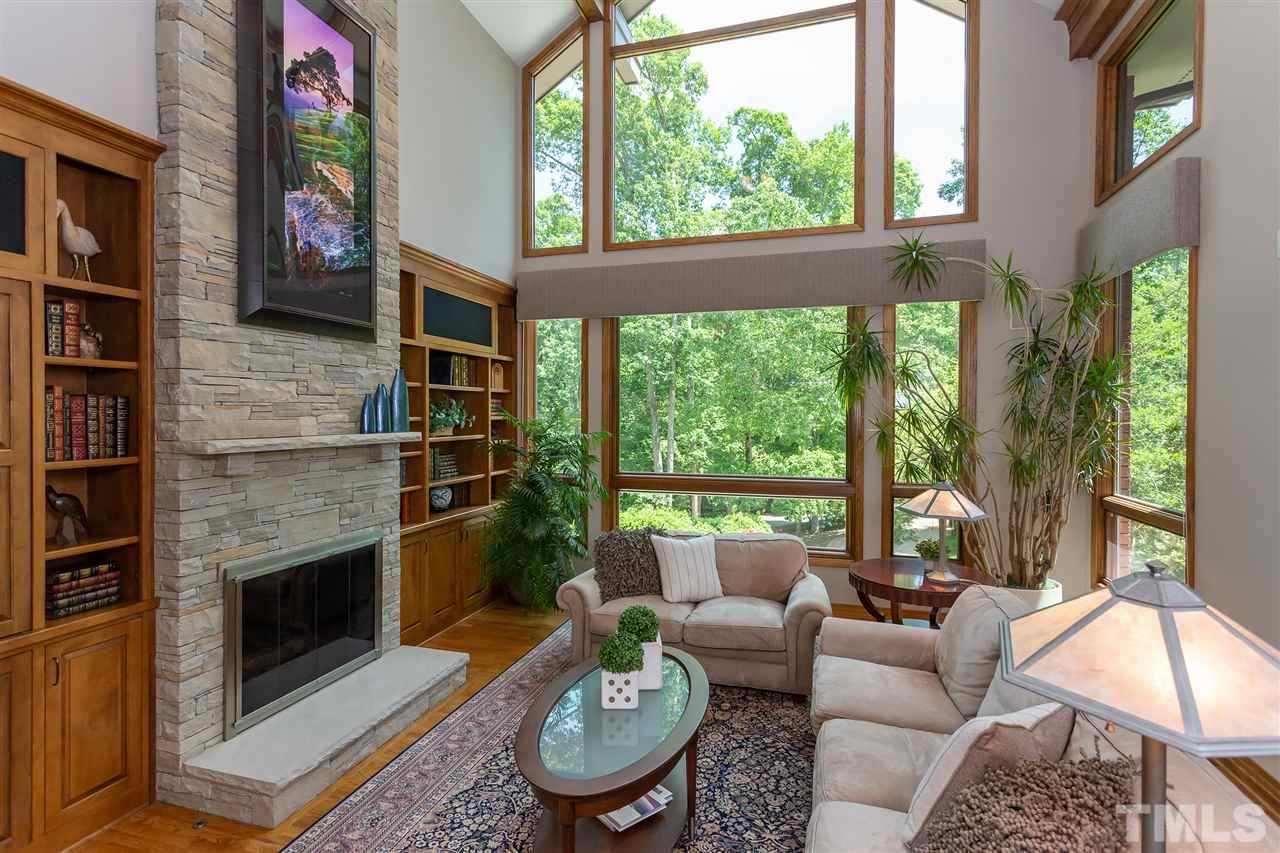 The family room is dominated by an incredible soaring stone fireplace.  This is flanked by striking built-in cabinets. Also there is a wet bar.