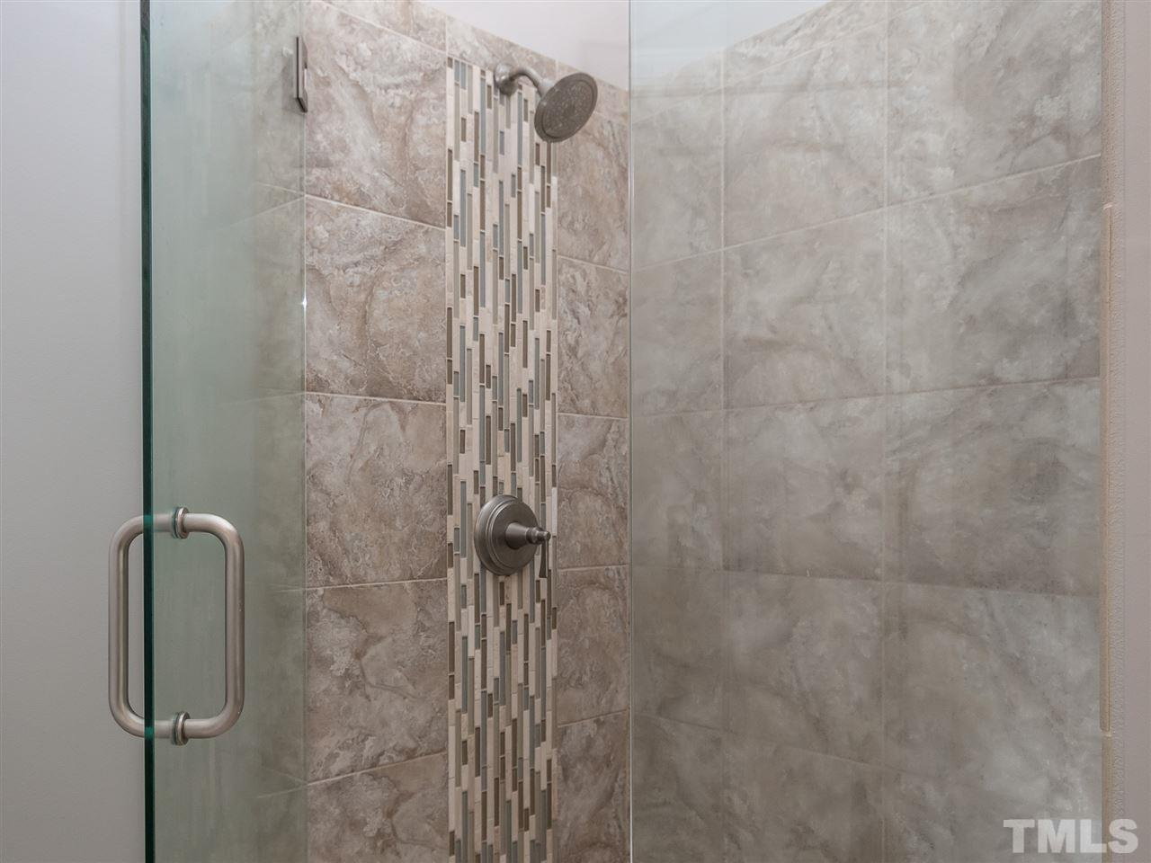 Newly tiled walk-in shower with glass door.