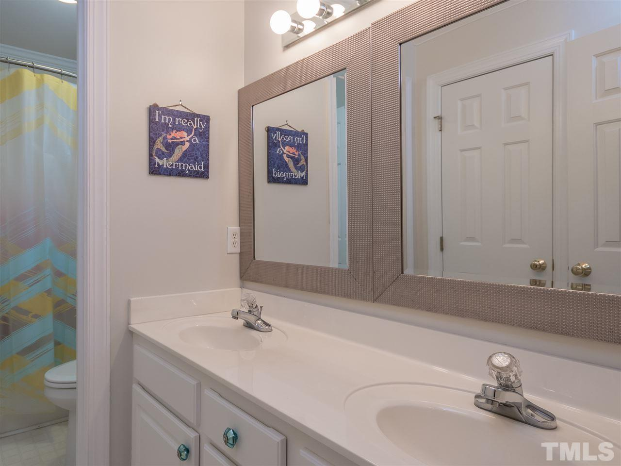 Hall bathroom for the secondary bedrooms - dual vanities, separate tub/shower and toilet room. Direct access from the hall and to the oversized bonus room next door.