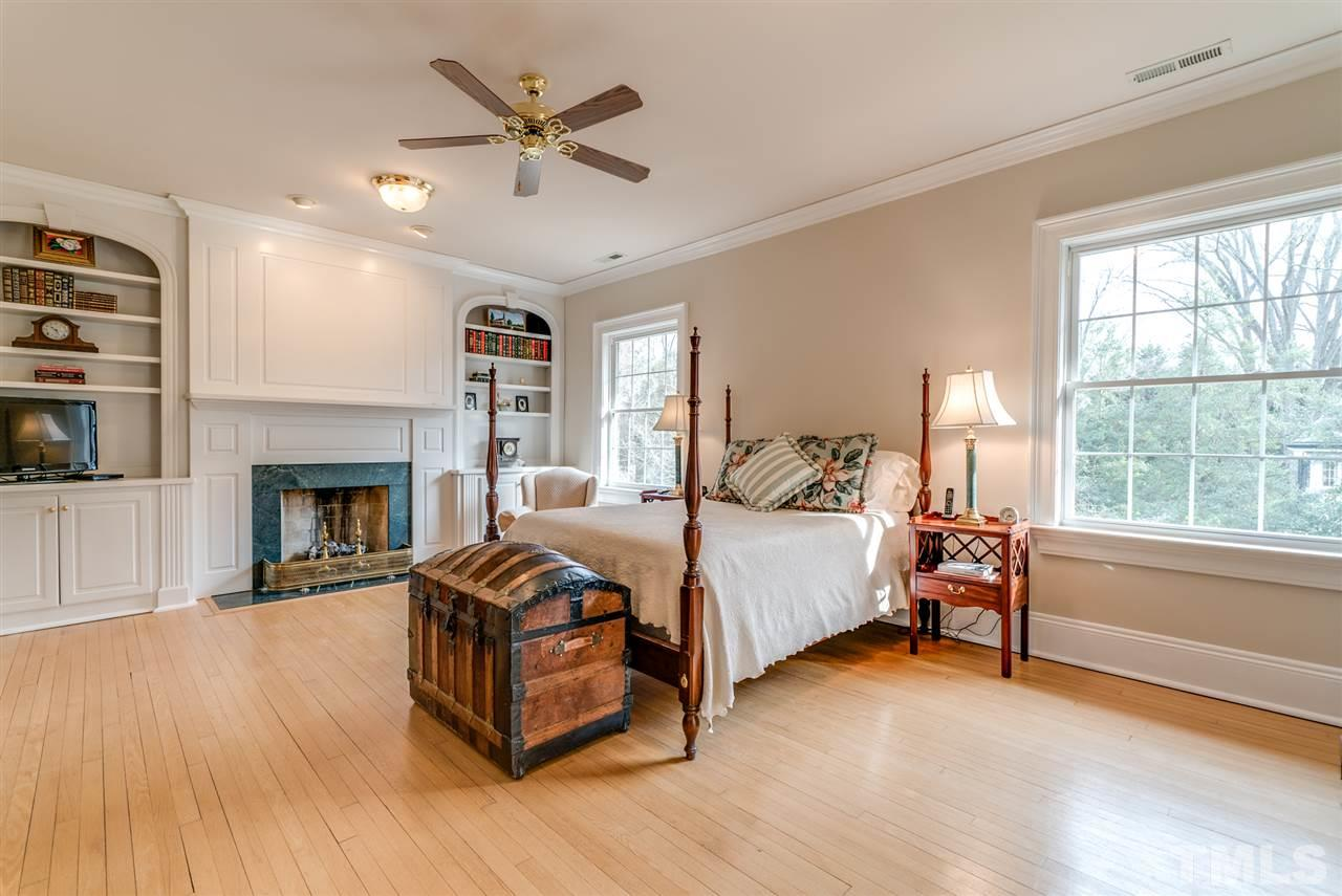 Spacious master bedroom with built in bookcase and cozy fireplace