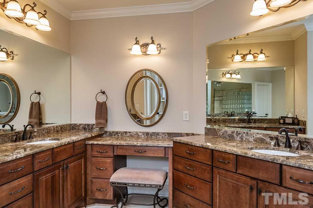 Separate vanities with plenty of counter space and storage in the large master bath.