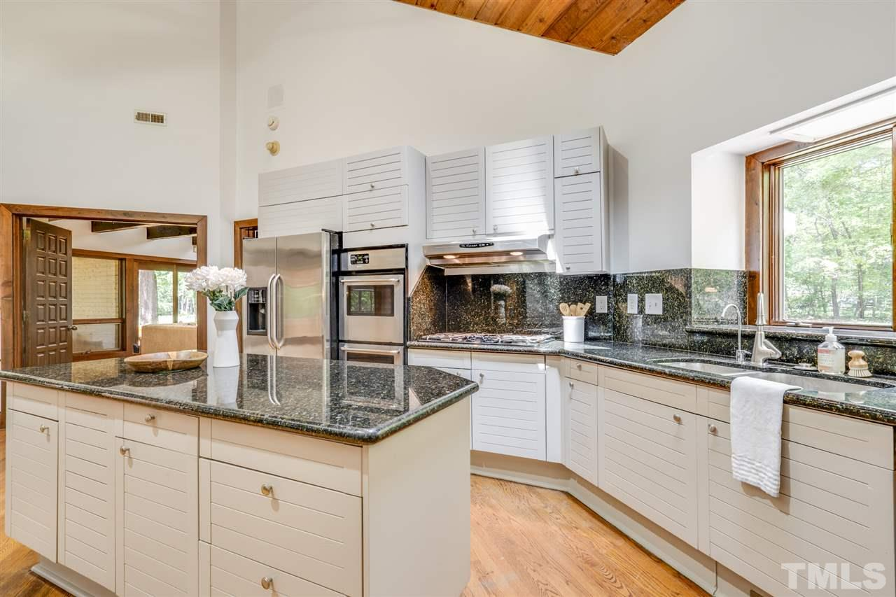 Skylights add beautiful light to this spacious kitchen. Window overlooks landscaped front yard.